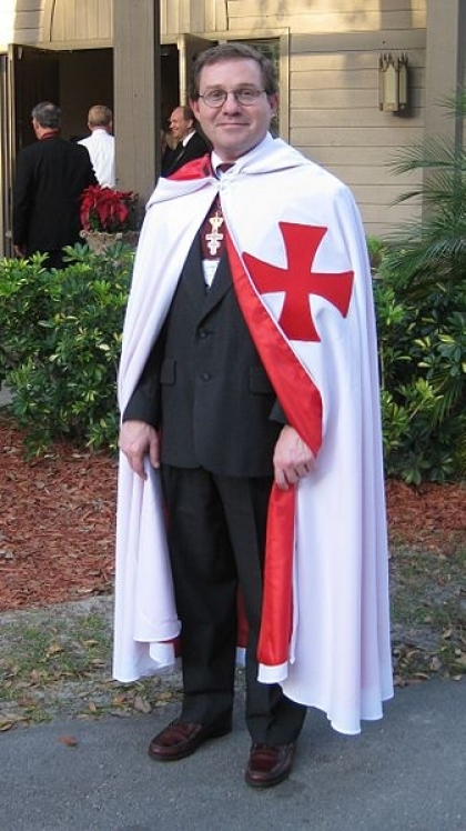 A man induced into the Knights Templar (Freemasonry) in 2009. Note the Maltese Cross. CC Danny Thompson https://commons.wikimedia.org/wiki/File:Templar_induction_2009_3.jpg#mw-jump-to-license