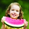 Beautiful little girl eating a juicy slice of watermelon