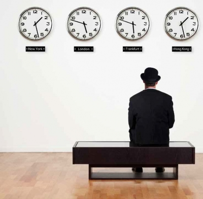 man waiting in front of clocks