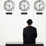 Man sitting and waiting by clocks