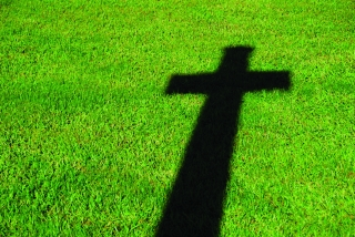 A stark shadow of a Christian cross is projected on a lush green lawn.