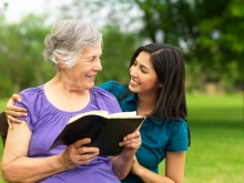 elderly woman with younger woman smile over a book
