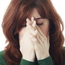 depressed young woman suffering stress and pain covering her face with hands