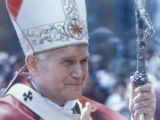 "<p>Pope John Paul II wearing a fish mitre, and carrying a staff with both a bent cross and a pine cone fertility symbol. Notice the four-spoked solar symbol on his mitre and the Maltese cross on his robe. <br /><br />Page 37 of Catholic historian Theodore Maynard's <em>The Story of American Catholicism</em> says, """"It has often been charged..that Catholicism is overlaid with many pagan incrustations. Catholicism, it must be added, is ready to accept the accusation—and even to make it her boast."" <br /><br />Note also the arms of Jesus shaped down into a ""V"" on the Pope's staff. This is a sign used in occultism to show victory over the Son of God. </p>"